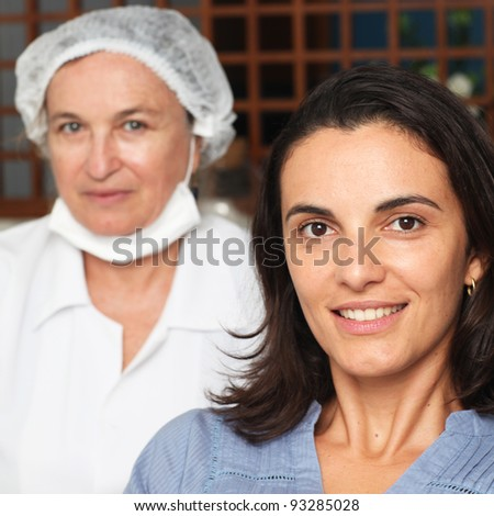 Female patient smiling while dentist with the equipment in the back - stock photo