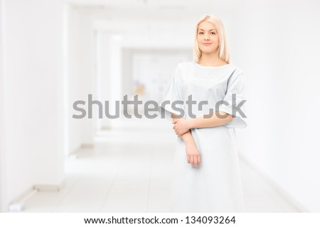 Female patient wearing hospital gown and posing in a hospital corridor - stock photo
