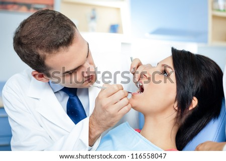 Female patient with dentist and assistant - dental treatment
