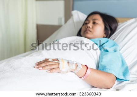 Female patient with IV drip needle piercing on hand in hospital room, Focus on hand - stock photo