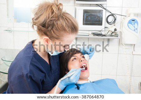 Female patient with open mouth receives dental treatment at the dentist while sitting on chair - stock photo