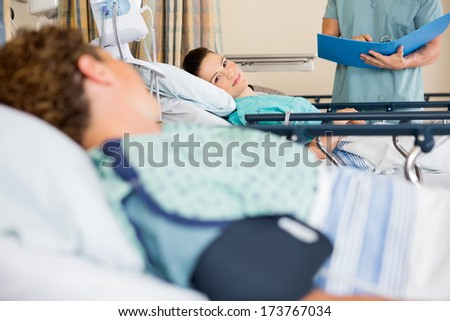 Female patients looking at each other while nurse standing in hospital ward - stock photo