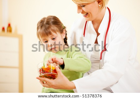 Female pediatrician doctor giving candy (gummy bears) to little patient after the treatment