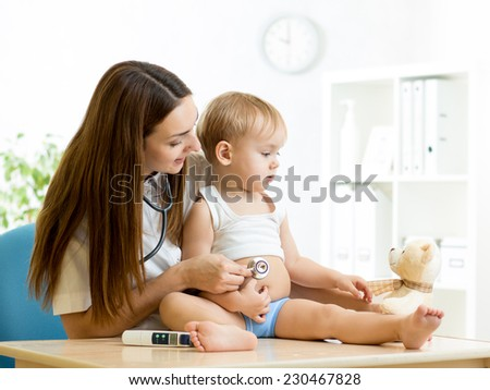 female pediatrician examining of toddler kid in office - stock photo
