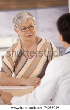 Female pensioner at doctors office listening to doctors explanation. - stock photo