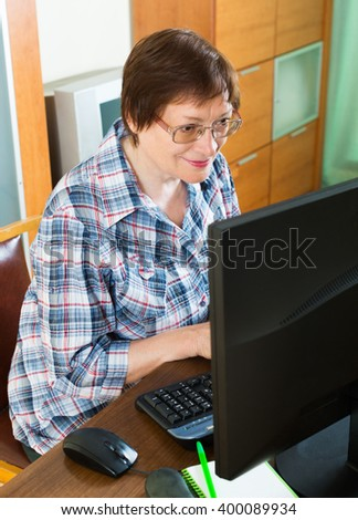 Female pensioner studying computer literacy in office interior