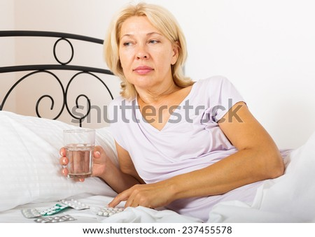 female pensioner taking medicine before falling asleep in bed - stock photo