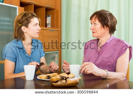 Female pensioner tea-drinking  with her daughter and having a chat indoor - stock photo