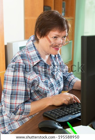 Female pensioner working with personal computer in office interior - stock photo