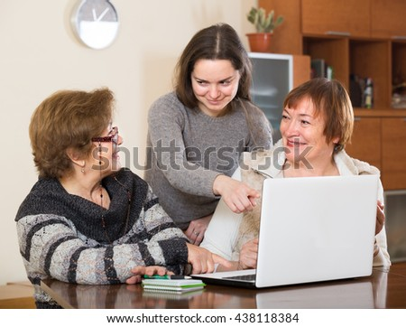Female pensioners and young relative making shopping list on laptop - stock photo