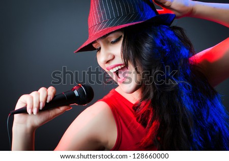 Female performer at disco with mic - stock photo