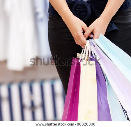 female person holding a shopping bags in a store