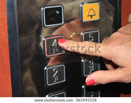 Female person pushing elevator button. - stock photo