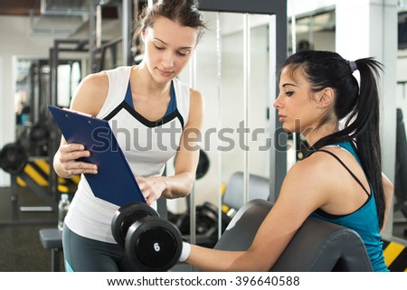 Female personal trainer helping young woman on her work out routines in gym. Fitness woman lifting weights and her personal trainer showing fitness report on a clipboard.