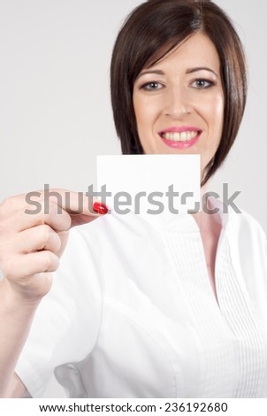 Female pharmacist holding a blank visiting card - stock photo