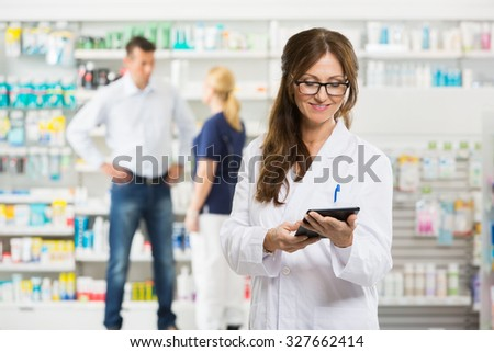 Female pharmacist holding digital tablet while assistant and customer standing in background at pharmacy - stock photo