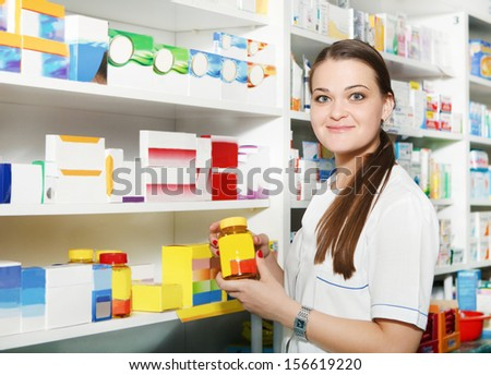 Female pharmacist holding out tablets in bottle at drugstore - stock photo