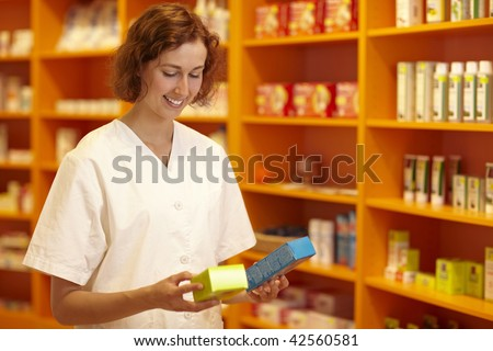 Female pharmacist looking at medicine in her hand - stock photo