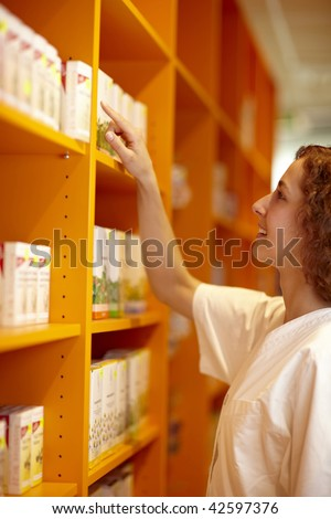 Female pharmacist looking for medicine in shelf