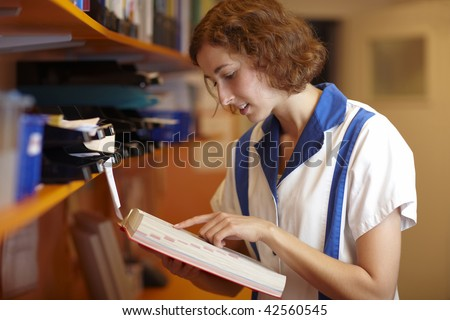 Female pharmacist reading in a red book