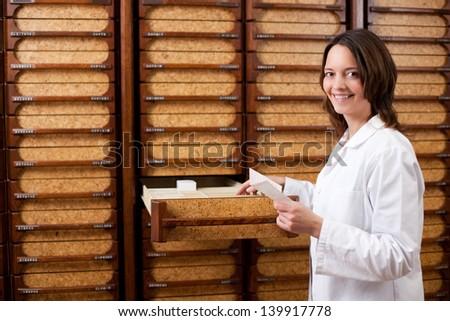 Female Pharmacist Searching Medicines In Shelf - stock photo