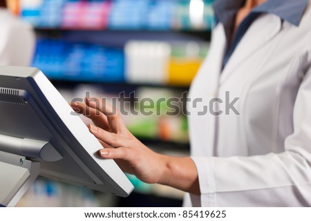 Female pharmacist standing at the cashier in pharmacy, only torso to be seen - stock photo