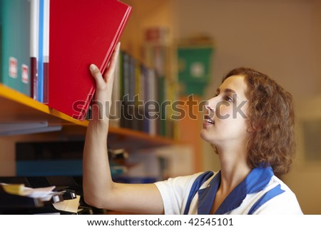 Female pharmacist taking red book from a shelf