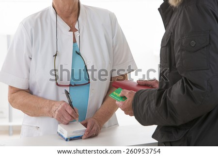 Female pharmacist talking to patient about the medical prescription - stock photo