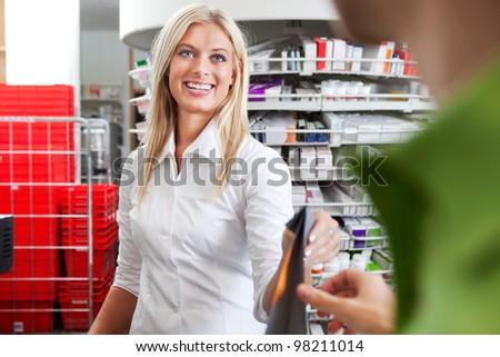 Female Pharmacist With a Male Customer in Pharmacy Drugstore. - stock photo