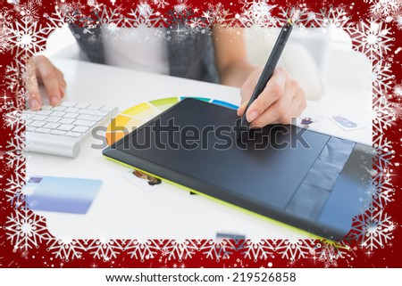 Female photo editor using graphics tablet against snow - stock photo