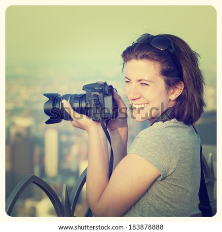 Female photographer at sunset taking city pictures with Instagram effect filter - stock photo
