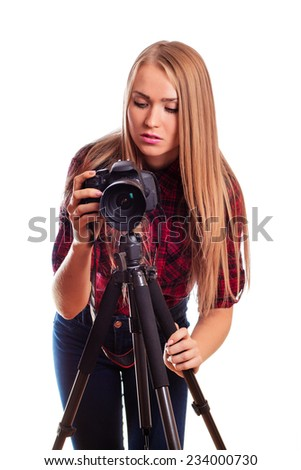 Female photographer holding a professional camera and making picture - isolated over white - stock photo