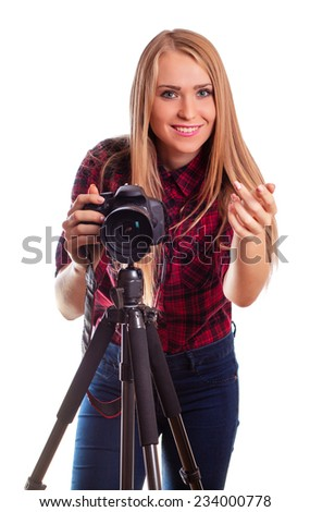 Female photographer holding a professional camera and taking images - isolated over white - stock photo