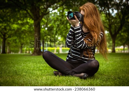 Female photographer sitting on grass at the park - stock photo