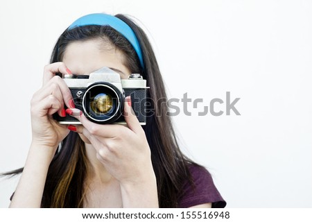 Female photographer taking photos with a vintage camera - stock photo