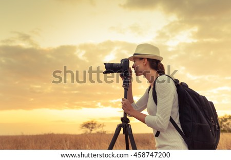 Female photographer taking pictures of the beautiful sunset.  - stock photo