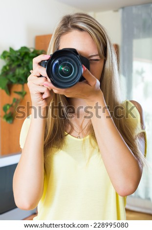 Female photographer testing new camera at office - stock photo