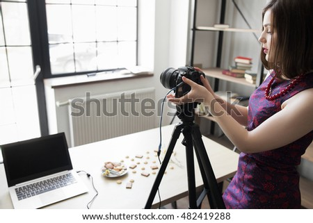 Female photographer tuning her camera at studio. Attractive young woman standing near her work equipment. Preparing for photographing