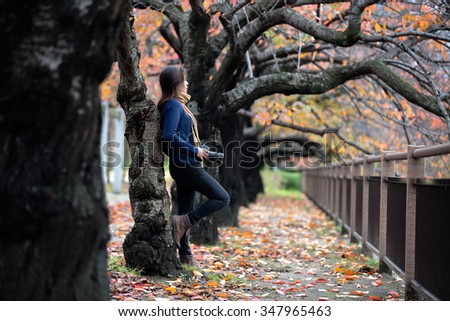 Female photographer with camera outdoors at the autumn park