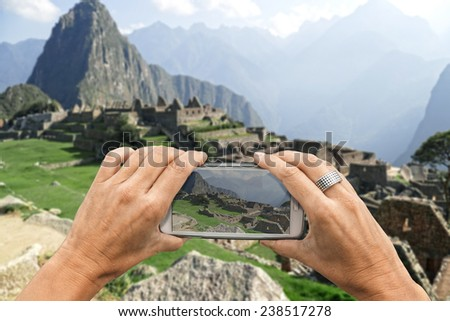 Female photographer with smartphone takes a picture of the Machu Picchu ruins - stock photo