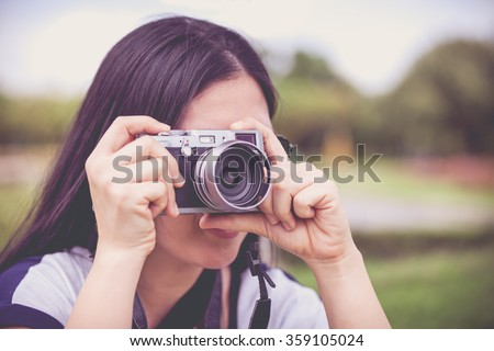 Female photographer with sunglasses holding professional digital camera vintage style. Asian woman taking picture on blurred nature background. Outdoor. - stock photo