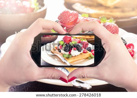 Female  photographing waffles with ice cream and berry fruits,selective focus  - stock photo