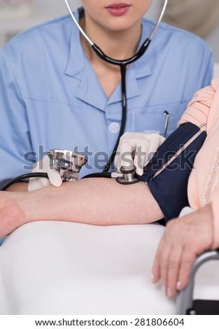 Female physician examining senior lady's blood pressure - stock photo