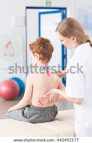 Female physiotherapist checks the mobility of the arm of boy