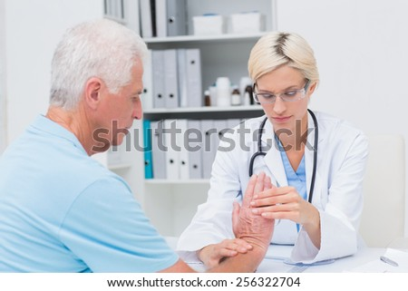 Female physiotherapist examining male patients wrist in clinic - stock photo