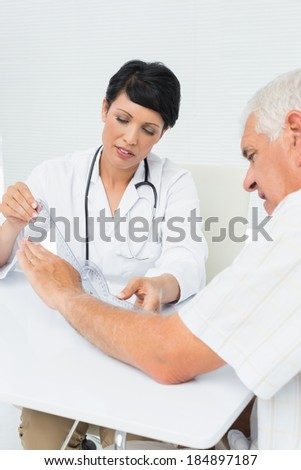 Female physiotherapist examining senior patients wrist with goniometer medical office