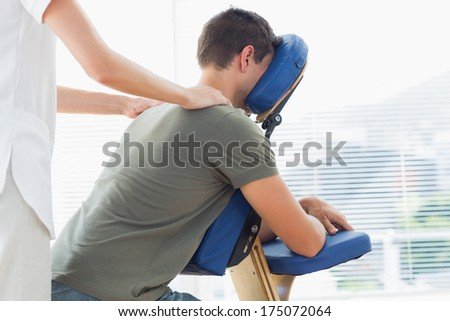 Female physiotherapist giving shoulder massage to man on massage chair in hospital - stock photo