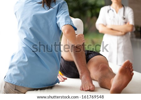 Female physiotherapist helping to exercise the patient injured knee - stock photo