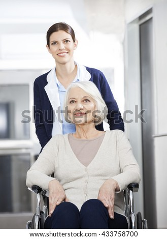 Female Physiotherapist Pushing Senior Woman In Wheelchair - stock photo
