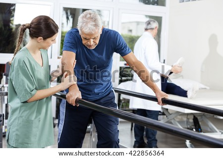 Female Physiotherapist Standing By Patient Walking Between Paral - stock photo